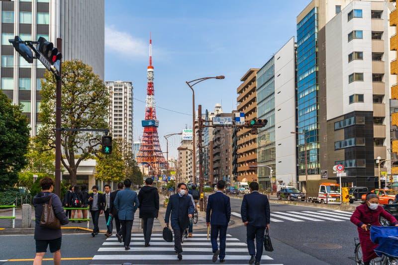 Unidendified people walk across the street in Tokyo city, Japan. TOKYO, JAPAN - March 25, 2019: TOKYO, JAPAN - March 25, 2019: Unidendified people walk across stock photography