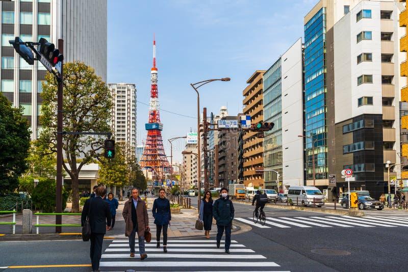 Unidendified people walk across the street in Tokyo city, Japan. TOKYO, JAPAN - March 25, 2019: TOKYO, JAPAN - March 25, 2019: Unidendified people walk across stock photo