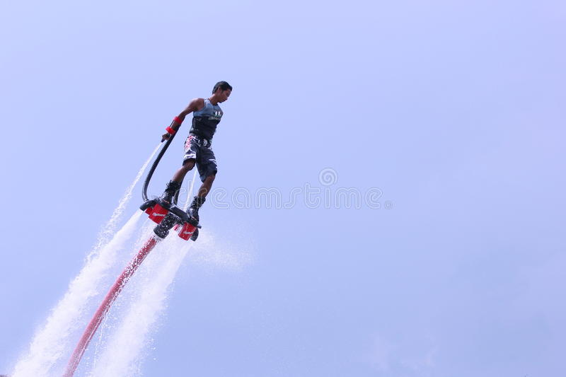 Unidentfied man demonstrates flyboard acrobatics, stock image