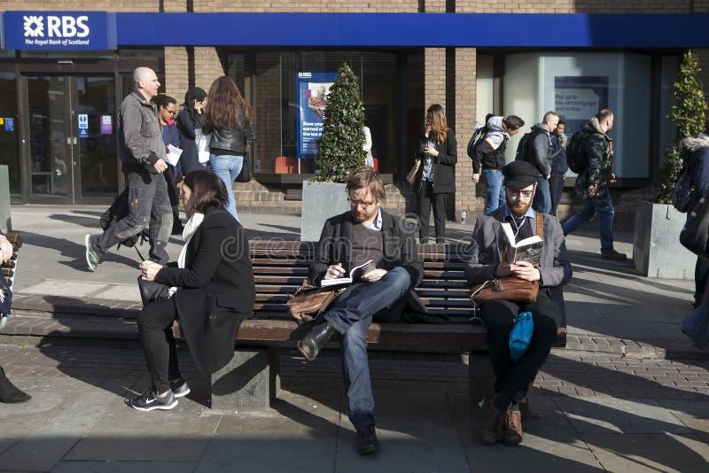 Unidentifed mężczyzna czytają książkę na ławce z turystami w tle Więcej niż 15 milionów ludzi wizyty Londyn każdego roku fotografia royalty free