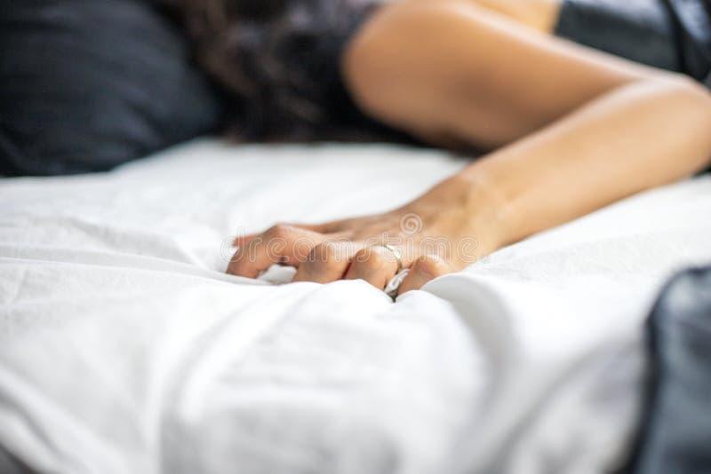 Unidentifiable gifta lögner för en kvinna i säng som bär en siden- nattlinne, medan hennes hand griper på till sängarken, sensual royaltyfri bild