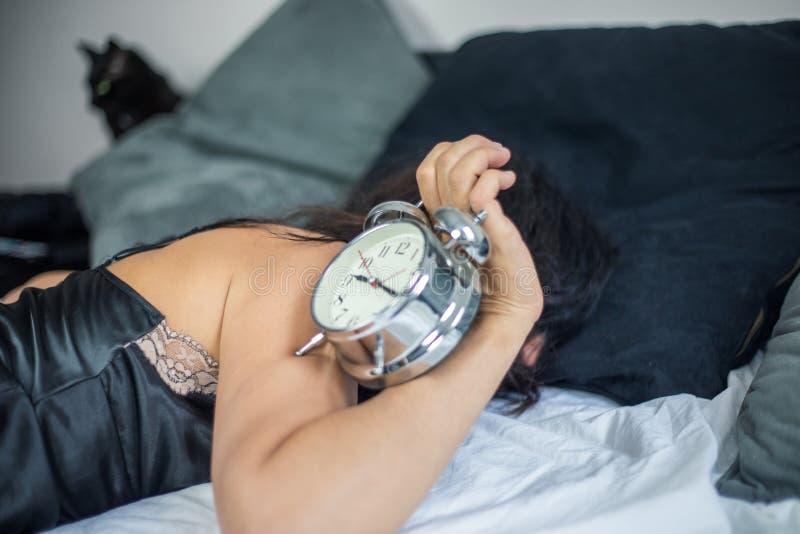 Unidentifiable kobieta jest ubranym jedwabniczą koszula nocną kłama w łóżku podczas gdy chwytający budzika obrazy royalty free