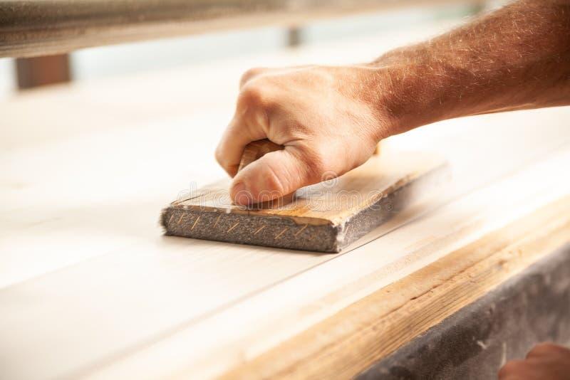 Unidentifiable mężczyzna sanding wielkiego kawałek drewno fotografia royalty free