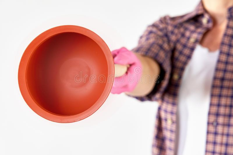 Unidentifiable person holding a red plunger. Unidentifiable person wearing pink latex gloves and holding out red rubber toilet plunger over white background stock photo