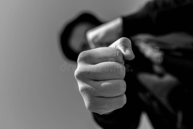 Unidentifiable tonårs- pojke som anfaller med kala händer för hes, fokus på näven i svartvitt arkivfoto