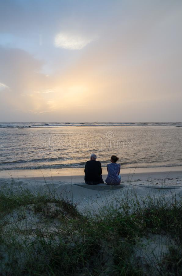 Unidentifieable middle age couple sitting on beach looking over the sea during sunset, Senegal, Africa royalty free stock photography