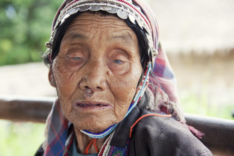 Unidentified Akha tribe. Elderly woman with traditional clothes and silver jewelery in hill tribe minority village, Thailand royalty free stock photos
