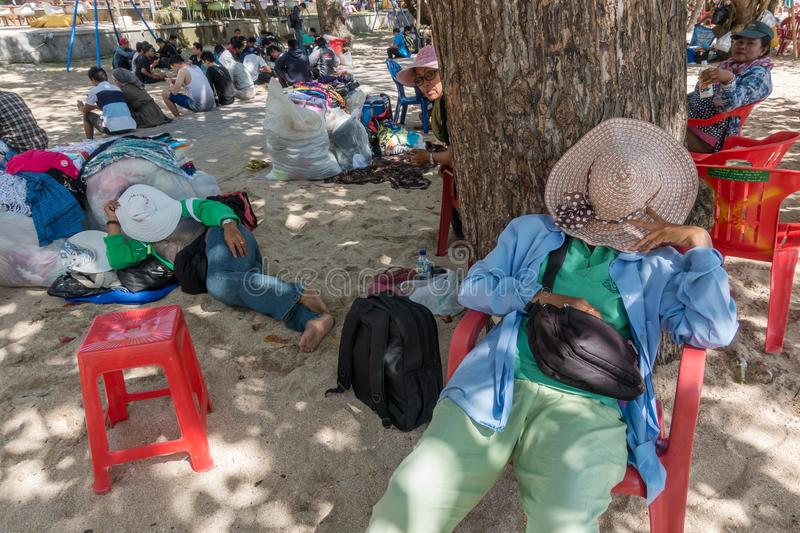 Unidentified balinese sarong vendors having rest in the shadow on the beach. stock image
