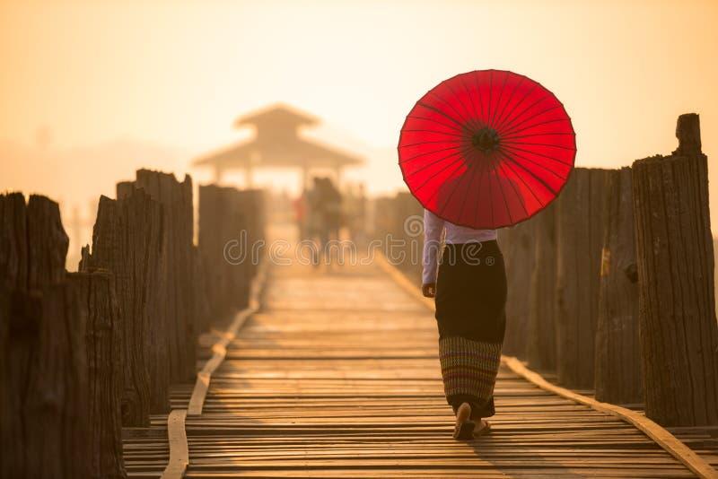 Unidentified Burmese woman walking on U Bein Bridge. Unidentified Burmese woman holding traditional red umbrella and walking on U Bein Bridge stock image