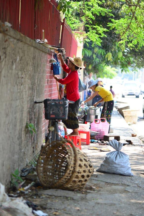 Unidentified Burmese women sells traditional street food in Myan. Yangon, Myanmar - May 5, 2014: Unidentified Burmese women sells traditional street food in royalty free stock photography