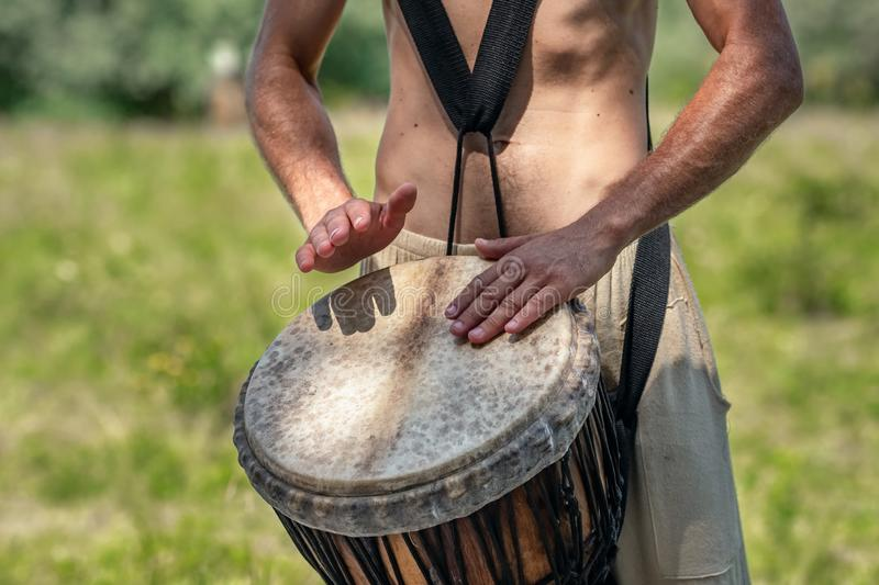 Unidentified caucasian man playing african djembe drum royalty free stock photography