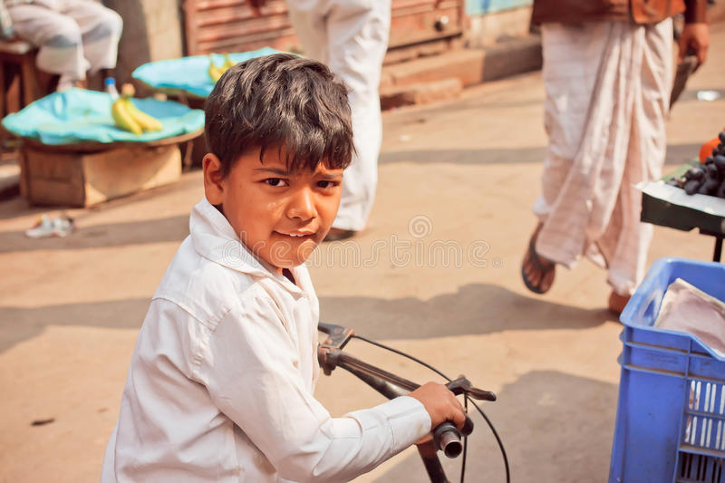 Unidentified cute kid on child bicycle driving outdoor in indian city stock photography