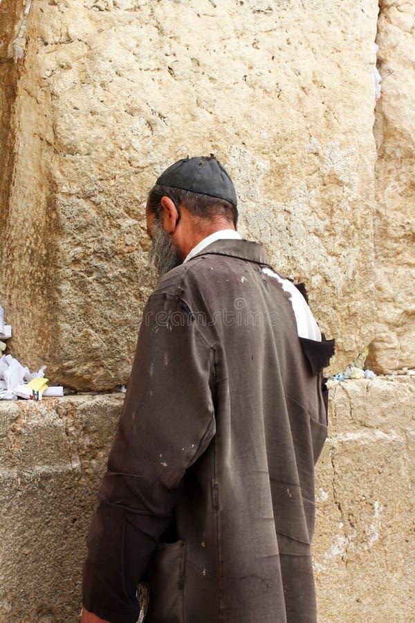 Unidentified fattig man som ber på den att jämra sig väggen arkivbilder