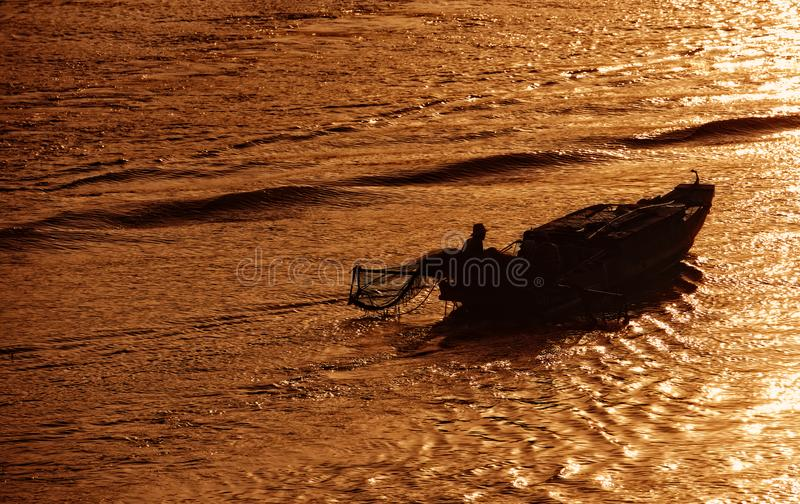 Unidentified fisher man check going with old boat in early morning on river in Ben Tre, Vietnam stock photo