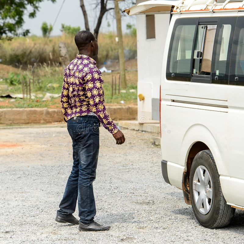 Unidentified Ghanaian man from behind stands near the car in lo. CENTRAL REGION, GHANA - Jan 17, 2017: Unidentified Ghanaian man from behind stands near the car royalty free stock photo