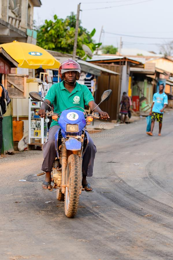 Unidentified Ghanaian man rides a motorcycle in local village. CENTRAL REGION, GHANA - Jan 17, 2017: Unidentified Ghanaian man rides a motorcycle in local royalty free stock photography