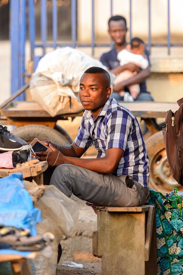 Unidentified Ghanaian man sells shoes on the market in local vi. CENTRAL REGION, GHANA - Jan 17, 2017: Unidentified Ghanaian man sells shoes on the market in royalty free stock photo