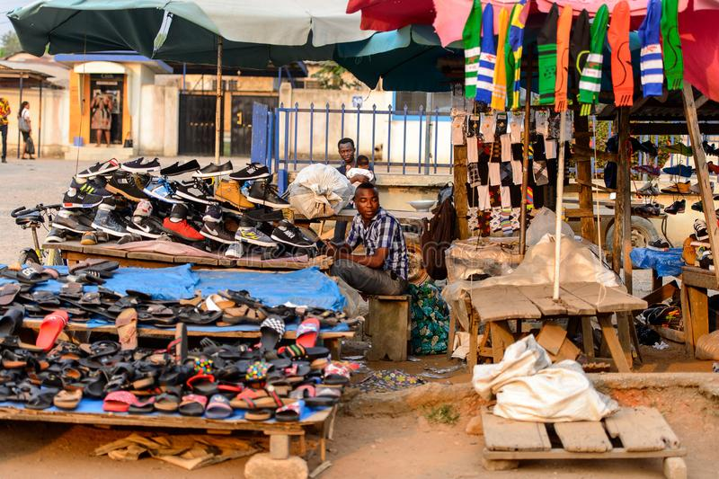 Unidentified Ghanaian man sells shoes on the market in local vi. CENTRAL REGION, GHANA - Jan 17, 2017: Unidentified Ghanaian man sells shoes on the market in royalty free stock photography