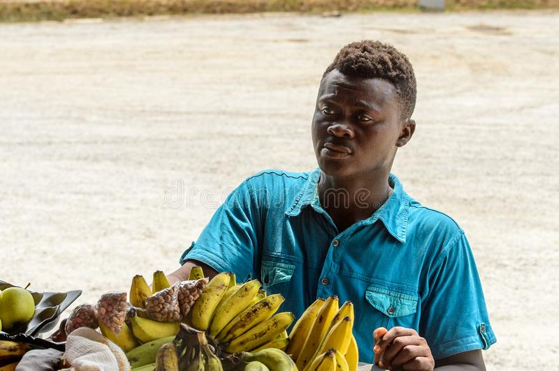 Unidentified Ghanaian man stands before the counter with fruits. CENTRAL REGION, GHANA - Jan 17, 2017: Unidentified Ghanaian man stands before the counter with royalty free stock photos