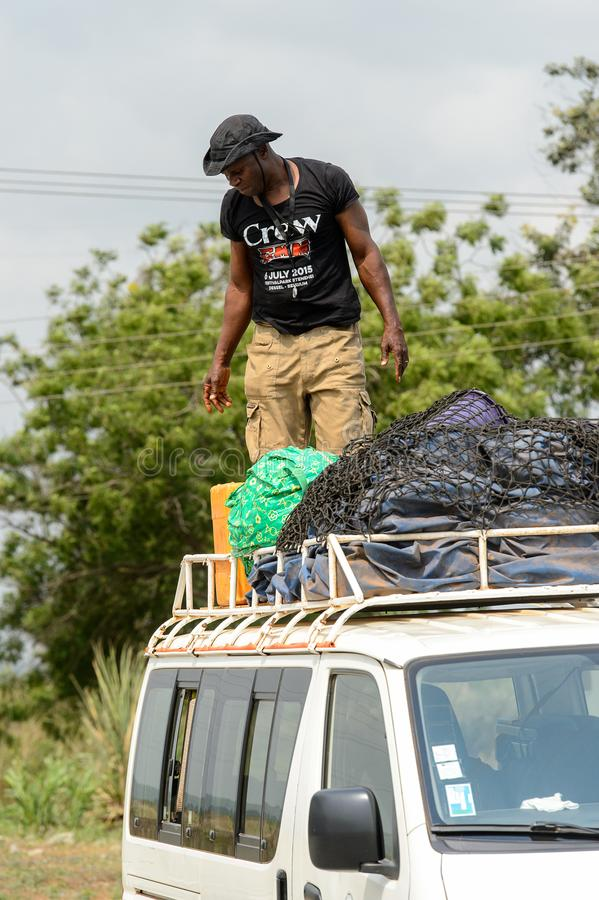 Unidentified Ghanaian man stands on the roof of the car in loca. CENTRAL REGION, GHANA - Jan 17, 2017: Unidentified Ghanaian man stands on the roof of the car in stock photo