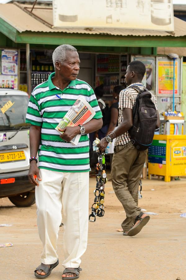 Unidentified Ghanaian man in striped shirt holds a newspaper in. CENTRAL REGION, GHANA - Jan 17, 2017: Unidentified Ghanaian man in striped shirt holds a royalty free stock photography