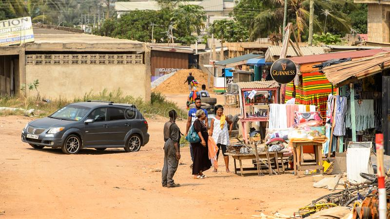 Unidentified Ghanaian people walk on the market in local villag. CENTRAL REGION, GHANA - Jan 17, 2017: Unidentified Ghanaian people walk on the market in local royalty free stock images