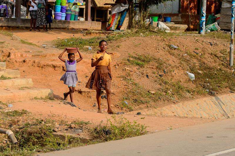 Unidentified Ghanaian two girls walk along the street in local stock images
