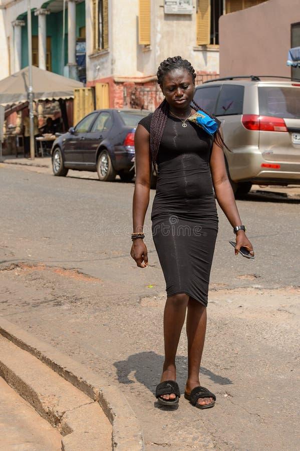 Unidentified Ghanaian woman in black dress with braids walks in. CENTRAL REGION, GHANA - Jan 17, 2017: Unidentified Ghanaian woman in black dress with braids stock image
