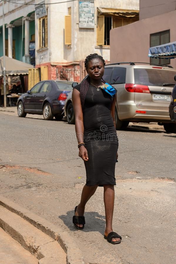 Unidentified Ghanaian woman in black dress with braids walks in. CENTRAL REGION, GHANA - Jan 17, 2017: Unidentified Ghanaian woman in black dress with braids stock photography