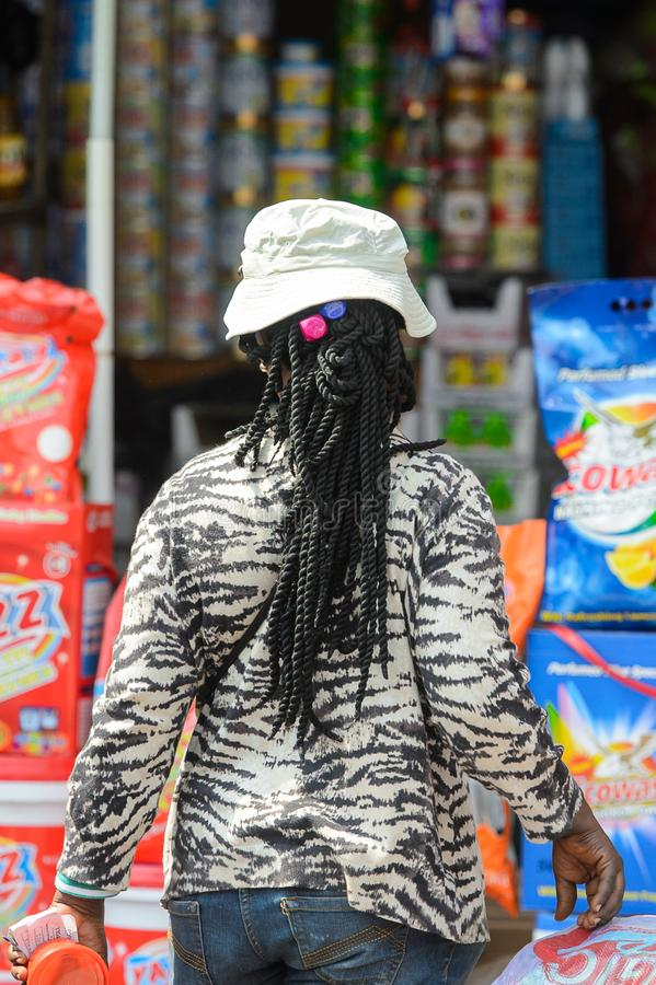 Unidentified Ghanaian woman with braids in a hat from behind in. CENTRAL REGION, GHANA - Jan 17, 2017: Unidentified Ghanaian woman with braids in a hat from stock image