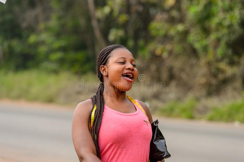 Unidentified Ghanaian woman in pink shirt with braids walks in. CENTRAL REGION, GHANA - Jan 17, 2017: Unidentified Ghanaian woman in pink shirt with braids walks stock photography