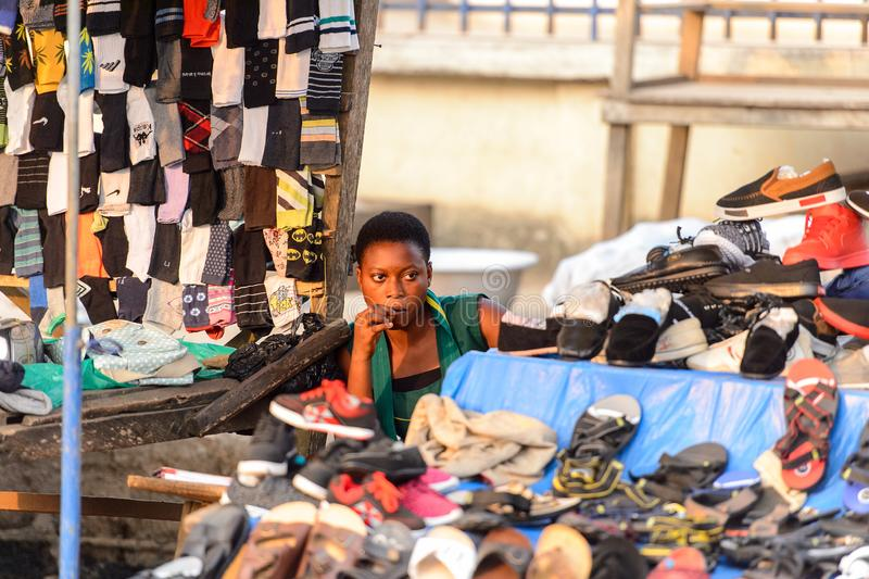 Unidentified Ghanaian woman sells shoes on the market in local. CENTRAL REGION, GHANA - Jan 17, 2017: Unidentified Ghanaian woman sells shoes on the market in royalty free stock photo