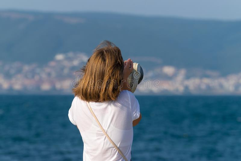 An unidentified girl looking through a tower viewer at sea in Nessebar, Bulgaria. A girl looking through a coin binocular, free. Use viewer, outdoor viewer 1 stock images