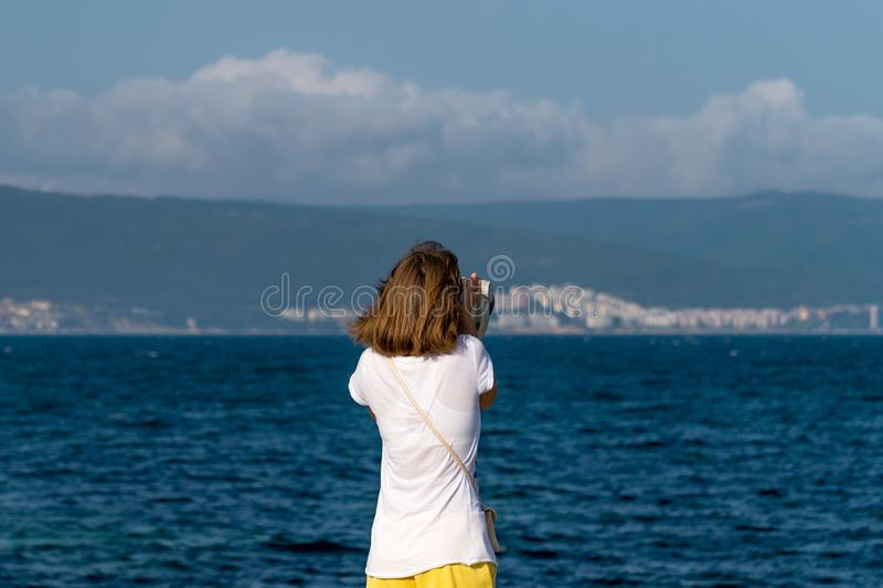 An unidentified girl looking through a tower viewer at sea in Nessebar, Bulgaria. A girl looking through a coin binocular, free. Use viewer, outdoor viewer 1 stock photos