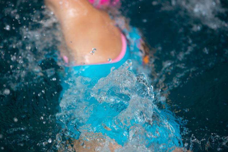 Unidentified girl swimming under water in a blue swimming pool. Abstract image with wavy pattern of sunlight on the rippling water. Top view, intense colors royalty free stock images