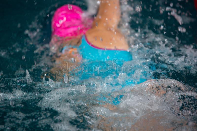 Unidentified girl swimming under water in a blue swimming pool. Abstract image with wavy pattern of sunlight on the rippling water. Top view, intense colors royalty free stock photo