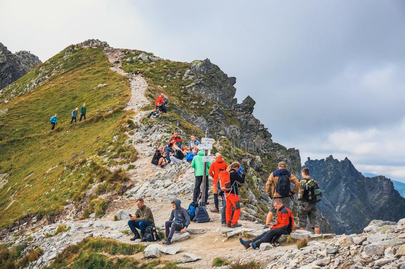 Unidentified group of hikers resting and exhausted at Krzyzne Pass in High Tatra Mountai. Tatra Mountains, Poland, August 14, 2017: Unidentified group of hikers stock images