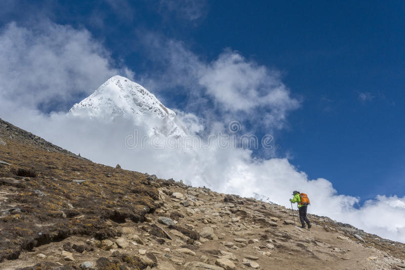 Unidentified hiker walking up tothe mountains area, during the way to Pumori mountains. Himalayas. royalty free stock photo