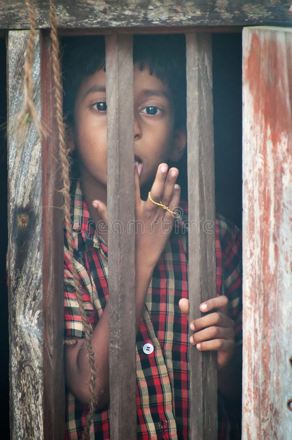 Unidentified Indian boy looks through window at. KOVALAM, INDIA, DEC 28, 2014: Unidentified Indian boy looks through a window at home in small fishing village royalty free stock photos