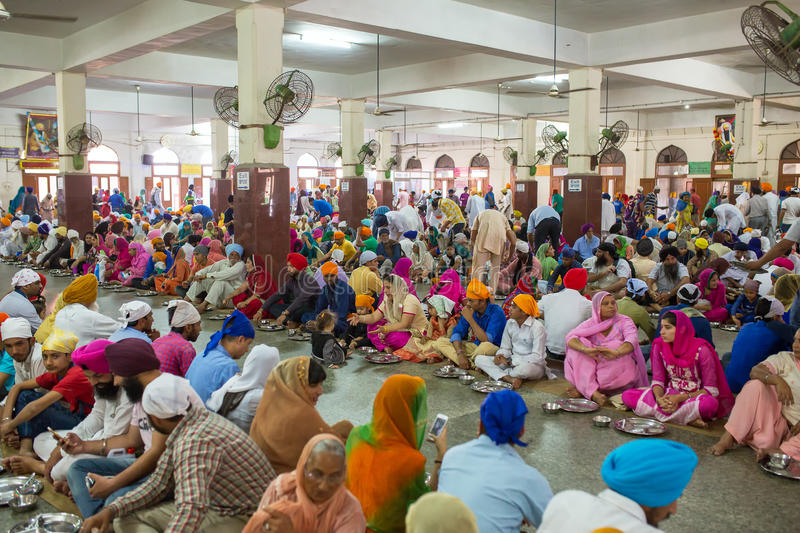 Unidentified indian people eating free food in the temple premises of Sikh Golden Temple in Amritsar. Amritsar, India - March 29, 2016: Unidentified indian royalty free stock photography