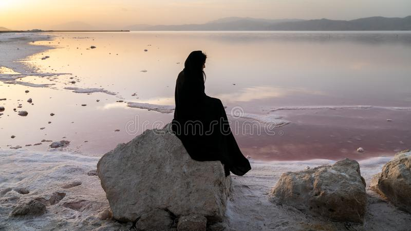 Unidentified Iranian woman in hijab burka sitting on a rock by the Maharloo pink lake, Shiraz, Iran stock photos