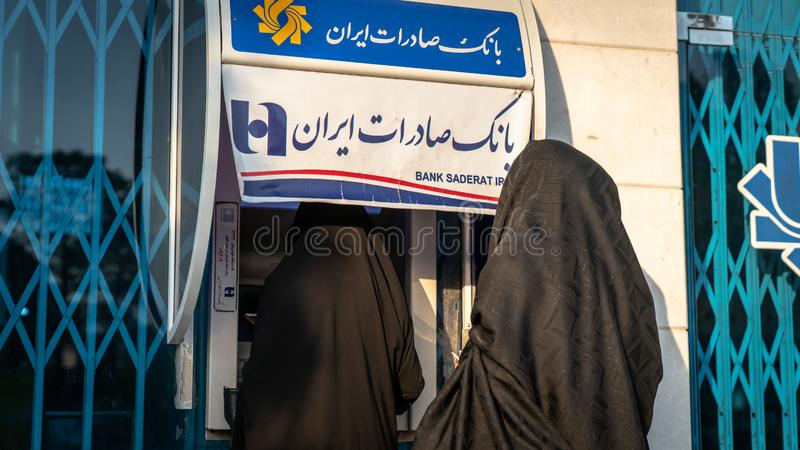 Unidentified Iranian women in hijab and burka using street ATM machines of Bank Saderat in Iran stock photography