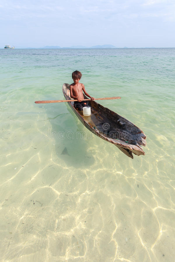 Unidentified kid on the canoes at Mabul island royalty free stock image