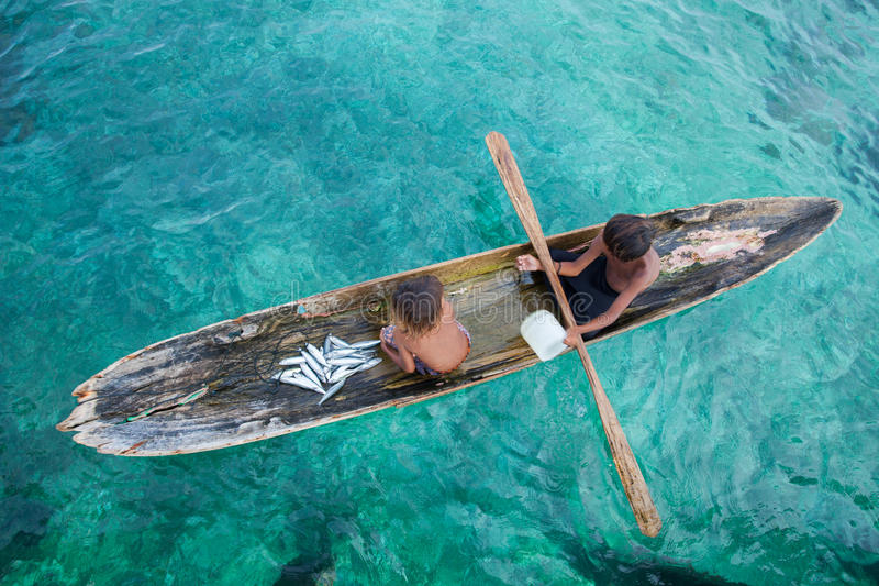 Unidentified kids on the canoes at Mabul island stock photography