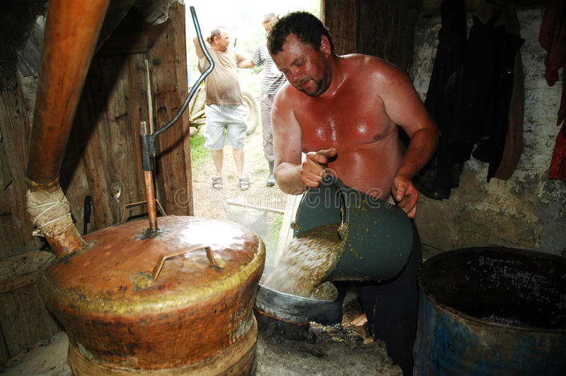 An unidentified local peasant distill apple brandy. BRATCA, ROMANIA - CIRCA JULY 2010: An unidentified local peasant with his young apprentice distill apple stock photo
