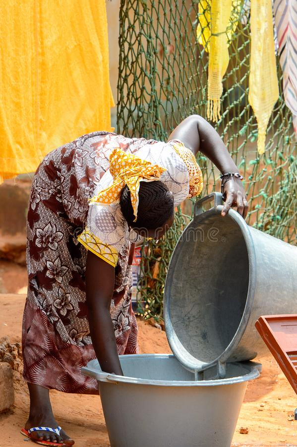 Unidentified local woman washes the basin in a village of the B. BUBAQUE, GUINEA BISSAU - MAY 5, 2017: Unidentified local woman washes the basin in a village of stock photos