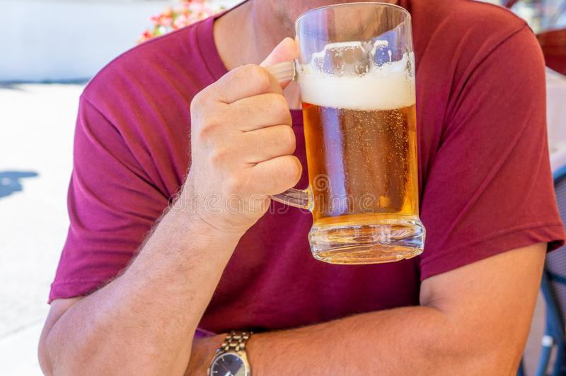 An unidentified man drinks out of a large glass mug of light beer on the background of a pub on a wooden table stock photos