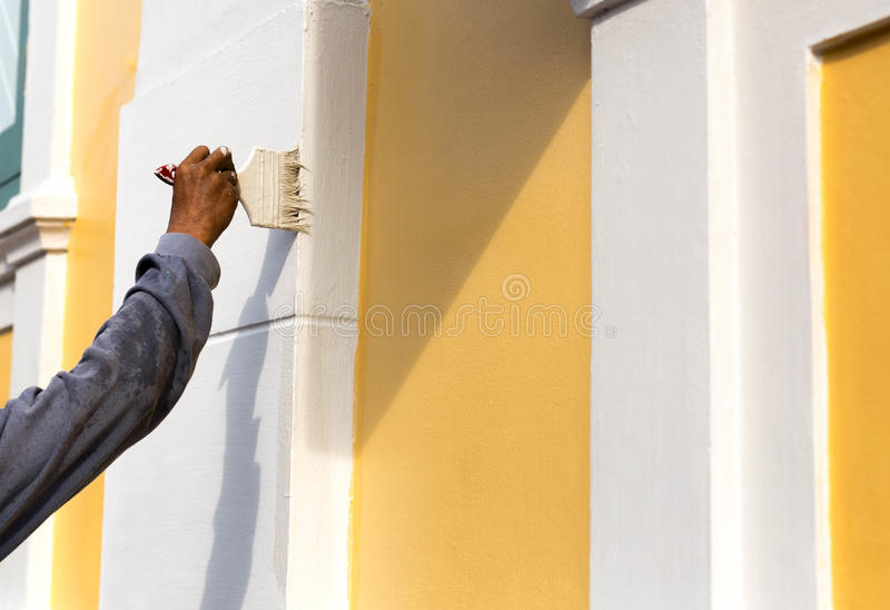 Unidentified man painting with brush on the building wall. Outside royalty free stock image