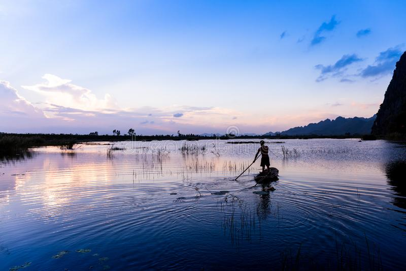 An unidentified man sailing a boat at sunset. On a lagoon in Ninhbinh, Vietnam royalty free stock images