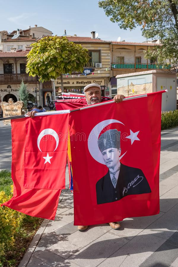 Unidentified man sells turkish national flags and flags with portrait of Ataturk, founder of Turkish Republic, on the. Antalya, Turkey - October 19, 2018 stock images